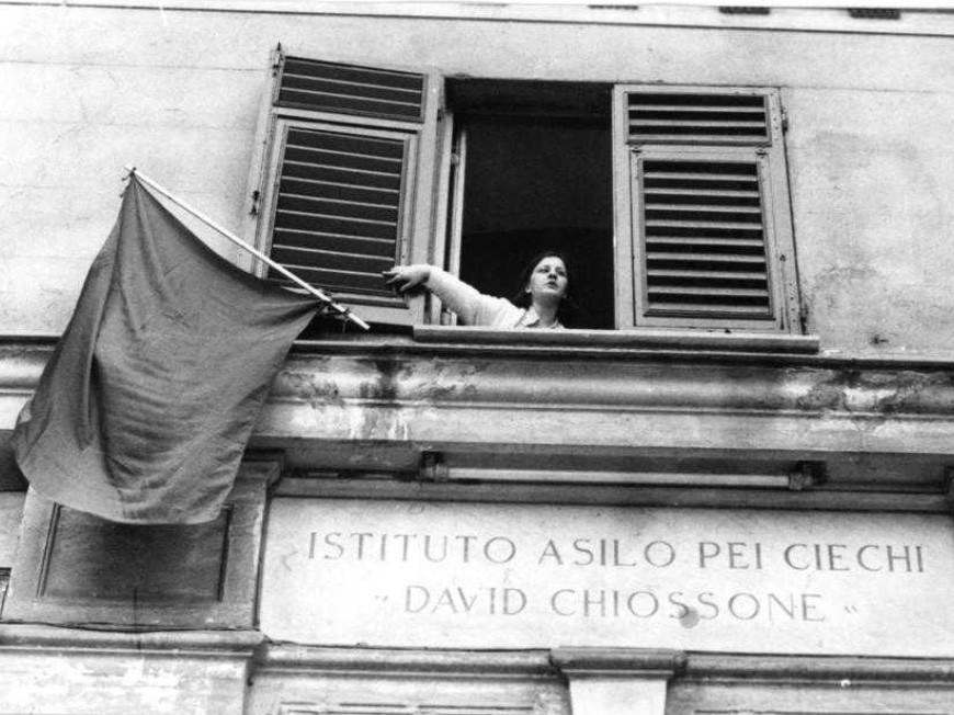 una ragazza cieca espone una bandiera rossa da una finestra sopra l'entrata dell'Istituto Chiossone